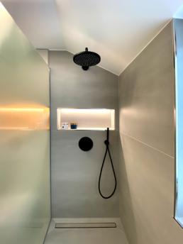 Eine große, begehbare Dusche mit schwarzen Armaturen und einer schwarzen Regendusche.