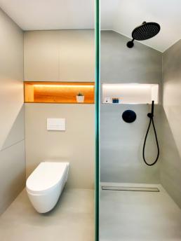 Eine große Glasfläche trennt den Nassbereich von dem Badezimmer ab.