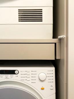 Eine Waschmaschine und ein Trockner befinden sich in dem großen Einbauschrank.